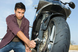 Young man changing motorcycle tire